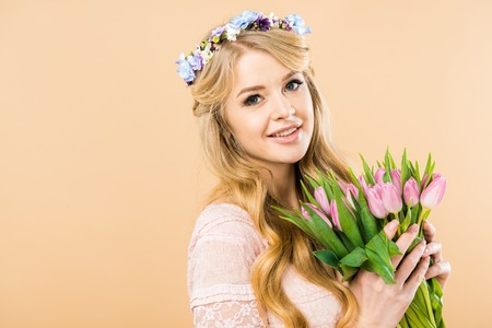 happy woman in colorful floral wreath holding pink tulips and looking at camera on yellow background