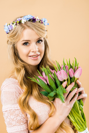 smiling woman in wreath of flowers holding bouquet of pink tulips and looking at camera on yellow background Stock Photo