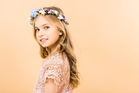 adorable child in elegant lacy dress and floral wreath smiling and looking at camera on yellow background Stock Photo