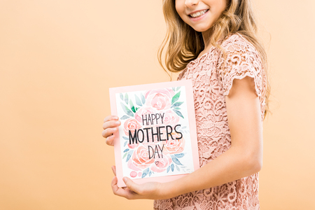 partial view of smiling child in pink lace dress holding happy mothers day greeting card on yellow background Stock Photo