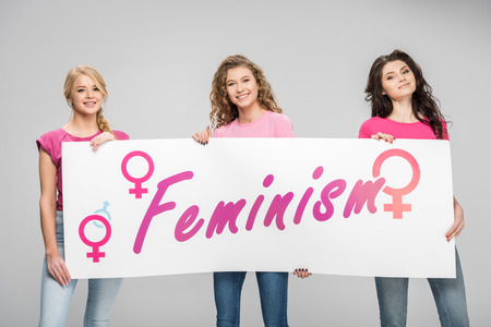 happy girls holding large sign with feminism lettering isolated on grey
