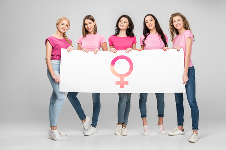 attractive young women holding large sign with female symbol on grey background
