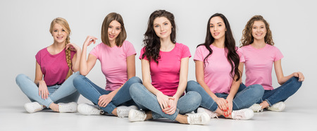 cheerful young women sitting on floor and smiling on grey background