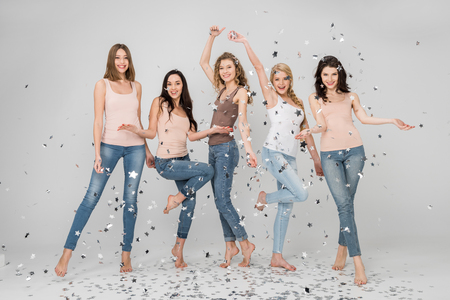 happy girls standing and smiling near confetti stars isolated on grey