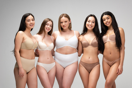 five beautiful multicultural girls in underwear looking at camera and smiling isolated on grey, body positivity concept Foto de archivo