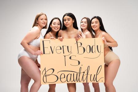 """cinq filles multiethniques souriantes tenant une pancarte avec le lettrage """"tout le monde est beau"""" isolé sur fond gris Banque d'images"""