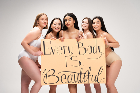 five smiling multiethnic girls holding placard with every body is beautiful lettering isolated on grey Stock Photo