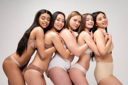 five happy young multicultural woman in underwear hugging each other isolated on grey, body positivity concept