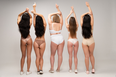 back view of five multicultural women in lingerie with raised hands, body positivity concept