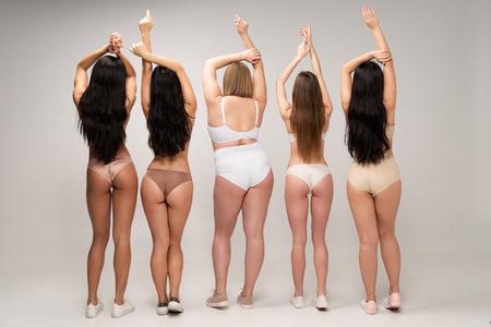 Vista posterior de cinco mujeres multiculturales en lencería con manos levantadas, concepto de positividad corporal Foto de archivo