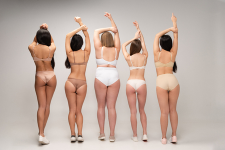 back view of five multiethnic women in underwear with raised hands, body positivity concept