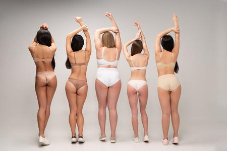 Vista posterior de cinco mujeres multiétnicas en ropa interior con manos levantadas, concepto de positividad corporal