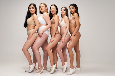 five beautiful multiethnic woman in underwear and sneakers posing at camera and smiling, body positivity concept