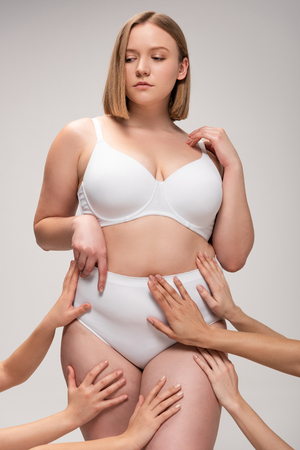 cropped view of female hands touching pretty overweight girl isolated on grey, body positivity concept