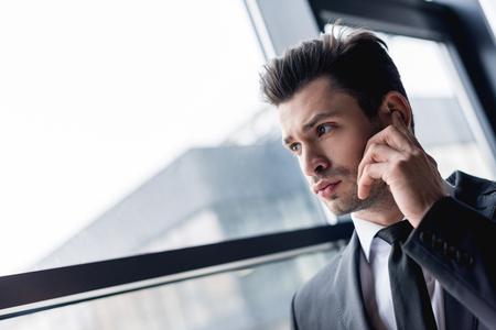 focused handsome bodyguard in suit using earphone Stock Photo