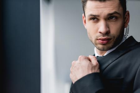 thoughtful bodyguard in suit using earphone