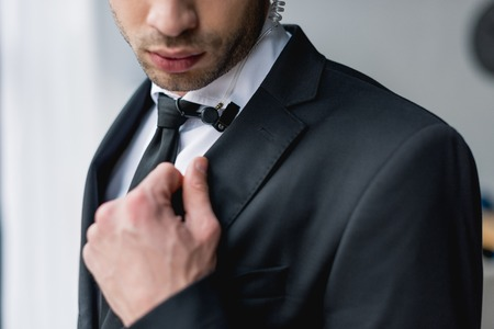 cropped view of bodyguard in suit using microphone