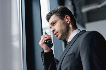 beau garde du corps en costume utilisant un talkie-walkie