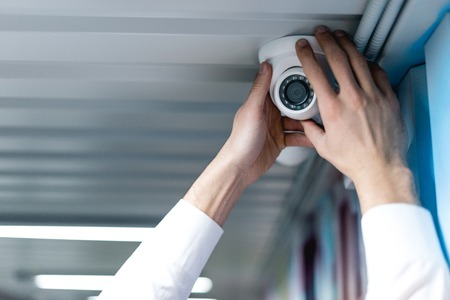 partial view of man setting up security camera Stock Photo