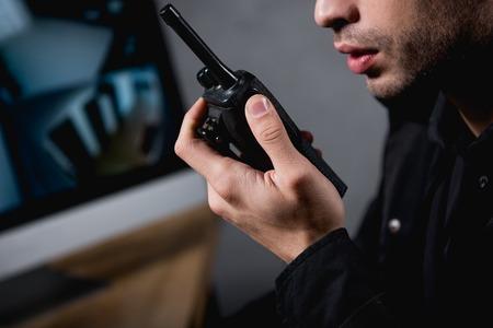 vue partielle de la garde tenant un talkie-walkie sur le lieu de travail
