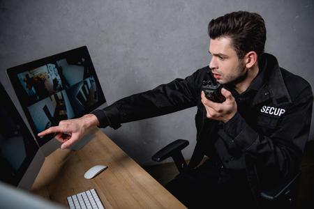 Guardia en uniforme hablando por un walkie-talkie y mirando el monitor de la computadora