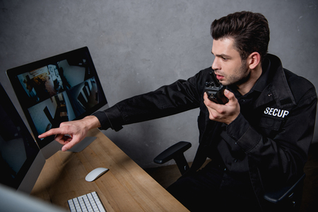 Wachmann in Uniform spricht über Walkie-Talkie und schaut auf den Computermonitor