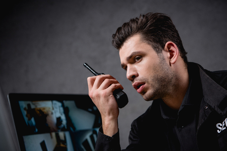 guard in uniform talking on walkie-talkie at workplace