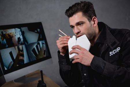 guard in uniform eating junk food and looking at computer monitor