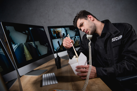 guard in uniform eating junk food and talking on telephone Stock Photo