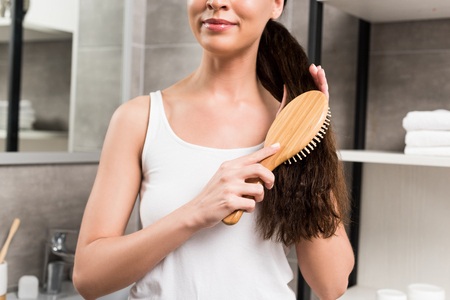 cropped view of smiling brunette woman brushing hair while standing in bathroom