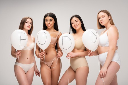 four attractive multiethnic women in lingerie holding air balloons with body lettering isolated on grey