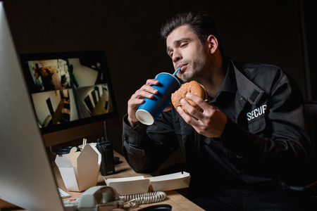 handsome guard drinking and eating burger at workplace Stock Photo