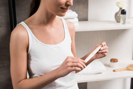 cropped view of happy woman holding pregnancy test in bathroom Stok Fotoğraf