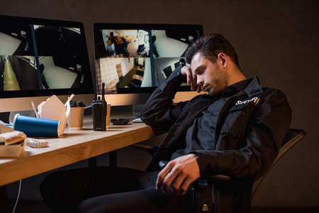 guard in black uniform sleeping at workplace
