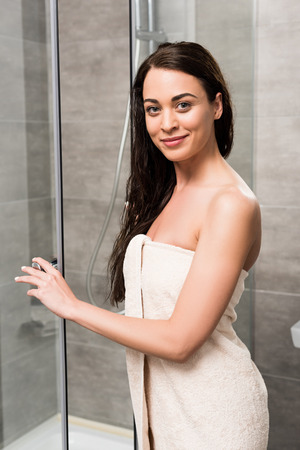 happy beautiful woman smiling while standing near shower cabin in bathroom