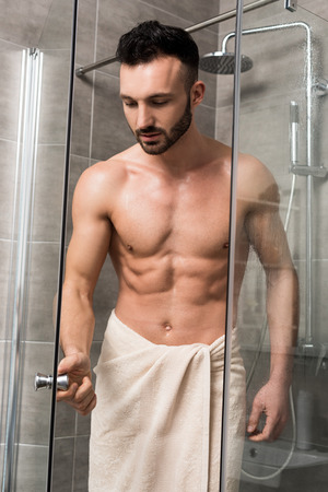 muscular handsome man standing in shower cabin in modern bathroom 版權商用圖片