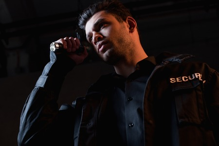 guard in uniform holding flashlight and looking away Stock Photo