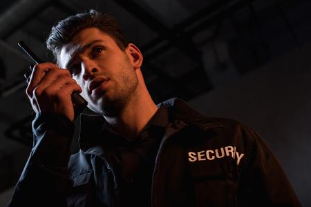 beau garde en uniforme utilisant un talkie-walkie et détournant les yeux