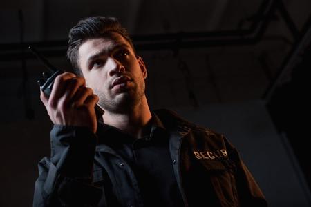 guard in uniform using walkie-talkie and looking away