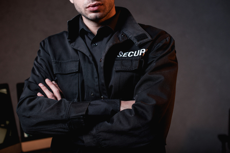 cropped view of guard in uniform with crossed arms at workplace Stockfoto