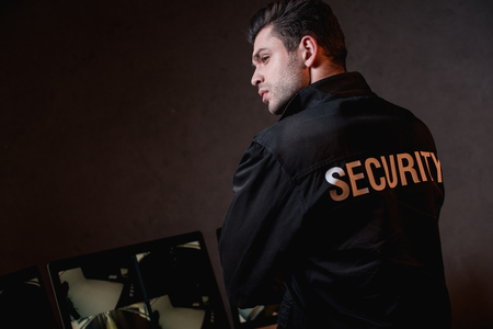 back view of guard in black uniform at workplace Stock Photo
