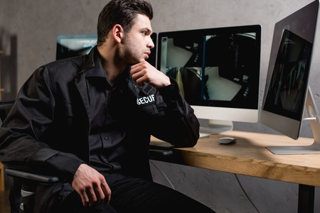 concentrated guard in uniform looking at computer monitor at workplace Stock Photo