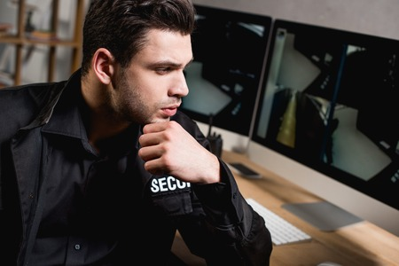 thoughtful guard in uniform looking at computer monitor at workplace