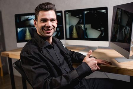 smiling guard in black uniform looking at camera Stock Photo