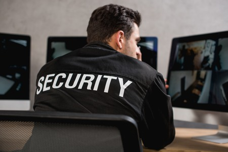 rear view of guard in black uniform looking at computer monitor Stock Photo