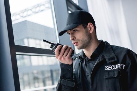 vista ritagliata della guardia in uniforme che parla al walkie-talkie e guarda lontano