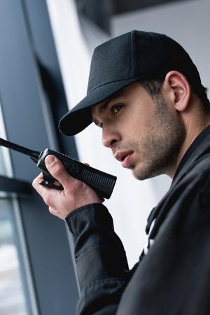 close up of guard in black uniform using walkie-talkie
