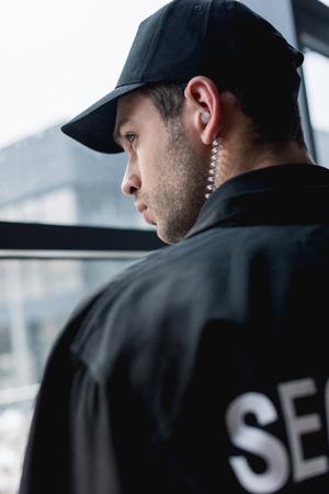 handsome guard in black uniform with earphone looking away
