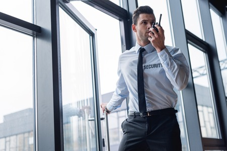 handsome guard in suit talking on walkie-talkie Stock Photo