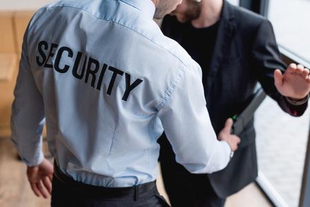 partial view of guard using metal detector